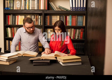 a man and a woman read books in the library are preparing for the exam 1 - Stock Photo