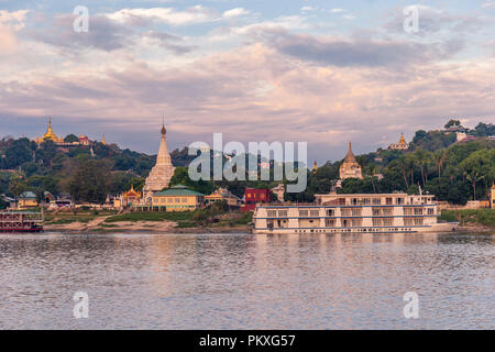 Pagodas gleam on the serene riverbanks of the Irrawaddy in Myanmar - Stock Photo