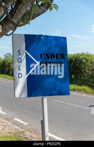 Property under offer and sold sign on a self standing board. - Stock Photo