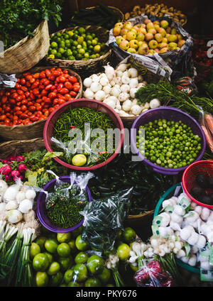 Autumn harvest of fresh organic vegetables on sale at a market stall - colorful bowls of tomato, beans, chillies, garlic, mushrooms, limes and apples