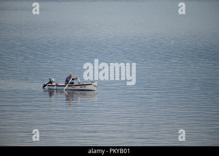 Old traditional fisherman in Croatia on a small wooden boat back into the harbor early morning - Stock Photo