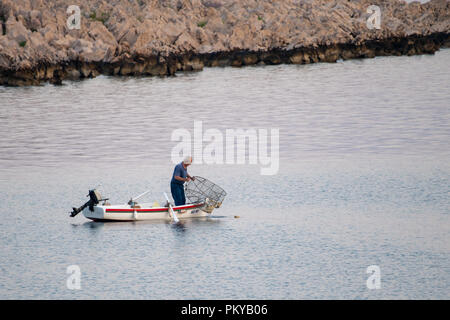 Old traditional fisherman in Croatia on a small wooden boat catching fish with fishing cage, pod - Stock Photo