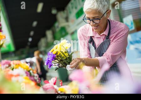 Charrming senior woman sales flowers on local market - Stock Photo