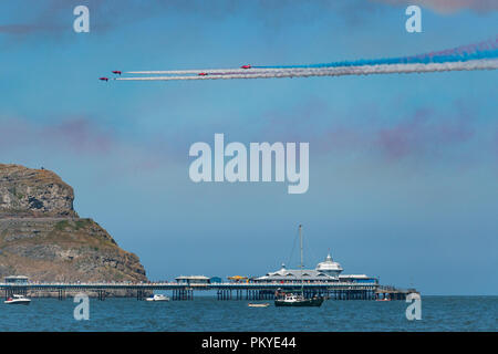 The Red Arrows perform the Corkscrew formation over the pier on Armed Forces Day at Llandudno - Stock Photo