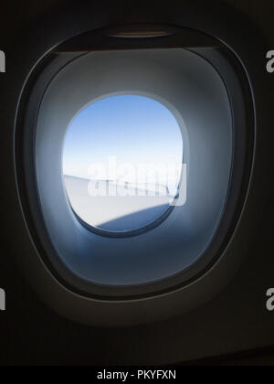 Looking out through the aircraft window of an Airbus A380 during intercontinental flight. - Stock Photo