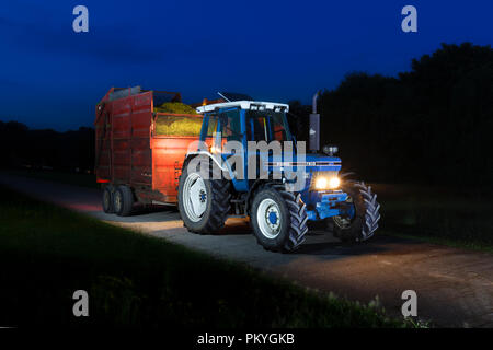 1991 Ford 7810 generation 3 tractor with  Teagle 8 tonne trailer being used by a farmer to carting silage on a dairy farm in the English countryside - Stock Photo