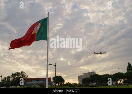 Blowing Portuguese flag on Square of Spain in Lisbon, looks like airport area, the aircraft taking off or landing nearby - Stock Photo