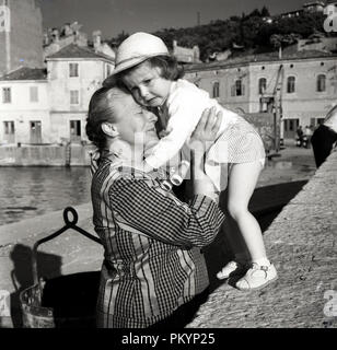 1950s, historical, by a small harbour, a grandmother holds and comforts a distressed little girl who thought she was lost, Italy. - Stock Photo