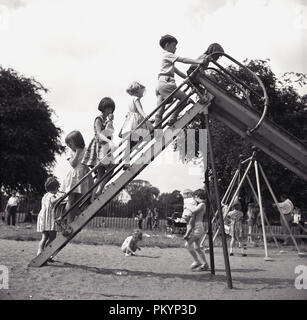 1950s, young boys and girls outside in a playground, climb the steps of a metal slide waiting their turn to go down, England, UK. - Stock Photo