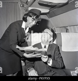 1960s, historical, a uniformed female flight attendant presenting a daily newspaper to a male passenger sitting in a business class seat on the aircraft. - Stock Photo