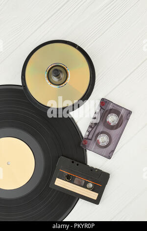 Vinyl record, compact discs and cassettes. Vinyl plate, DVD or CD disks and cassette tapes on wooden background, top view. Vintage musical devices. - Stock Photo