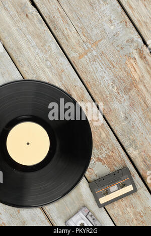 Vinyl record, cassettes and copy space. Vinyl lp and cassettes on old wooden background, top view. Music retro style. - Stock Photo