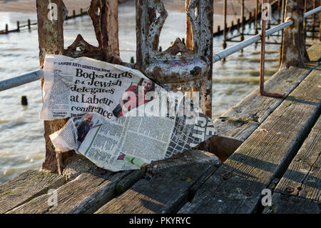 Windswept tabloid featuring an article about the Labour Party anti-antisemitism row stuck to the rusty side of an old jetty in Bognor Regis - Stock Photo