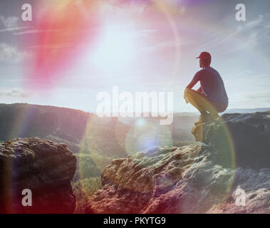 Hiker watching to Sun at horizon. Beautiful moment the miracle of nature. Colorful mist in valley. Man hike. - Stock Photo