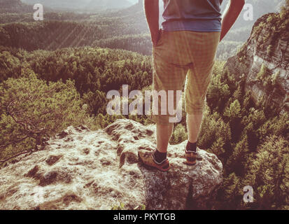 Hiker stays on a rocky ridge and enjoy view over long valley to horizon - Stock Photo