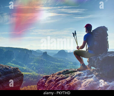 Man sitting on the rock cliff in mountain and watching on sunrise landscape. Nature composition. - Stock Photo