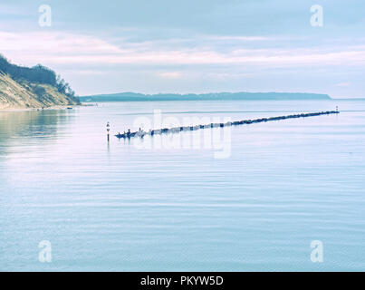 Timber groynes on the beach at the north sea. Moody blue sea - Stock Photo