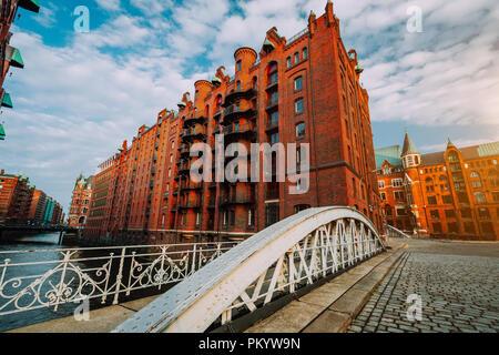 Arch bridge over canals in the Speicherstadt of Hamburg. Warm evening sun light on red brick building
