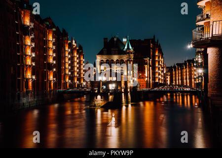 The Warehouse District - Speicherstadt at night. Tourism landmark of Hamburg. View of Wandrahmsfleet in light of lantern lamp. Port of Hamburg within the HafenCity quarter - Stock Photo