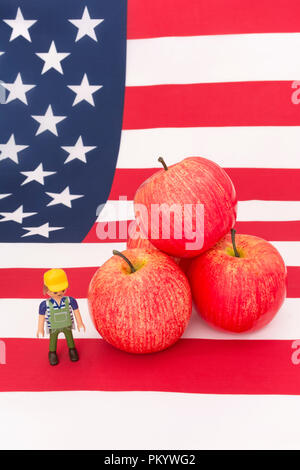 Red apples + U.S American flag / Stars and Stripes - metaphor US apple industry, Chinese trade tariffs on imports of American apples. Small toy farmer - Stock Photo