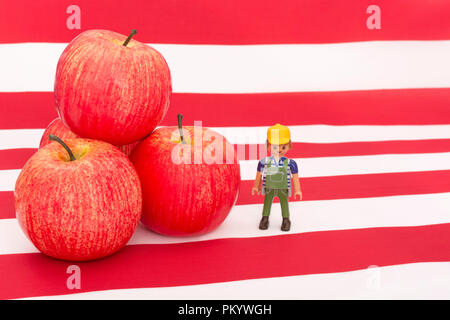 Red apples with U.S. American flag / Stars and Stripes - metaphor US apple industry, Chinese trade tariffs on imports of U.S. apples. Small toy farmer. - Stock Photo