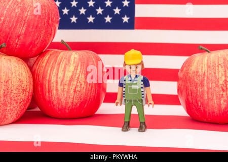 Red apples + US American flag / Stars and Stripes - metaphor US apple industry, Chinese trade tariffs on imports of American apples. Small toy farmer - Stock Photo
