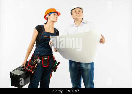 Portrait Of Male Architect And builder Woman Discussing building plan. foreman holding roll paper - Stock Photo
