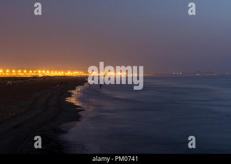 Long exposure landscape low light photo of beach in Valencia in Spain in early morning with city lights in background - Stock Photo