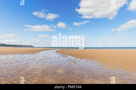 A wide stretch of water narrows as it runs to the sea across the beach.  A blue sky with clouds is above. - Stock Photo