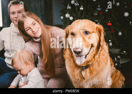 theme Christmas and New Year family circle and domestic pet. Mom dad and child 1 year old Caucasian woman sitting on floor near Christmas tree with gi - Stock Photo