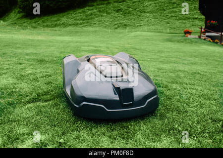 Robotic lawn mower on grass, automated lawn mower - Stock Photo