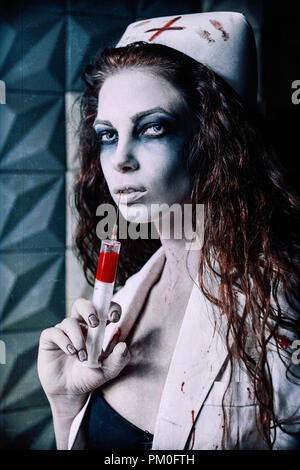 Horror shot: the scary evil nurse (doctor) with bloody syringe in hand. Zombie woman (living dead). Grunge texture effect - Stock Photo