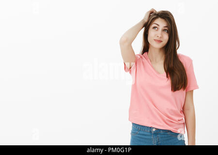 Portrait of unsure good-looking carefree female with dreamy expression, smiling and gazing up while scratching head, being clueless, thinking what to answer, standing over grey wall - Stock Photo