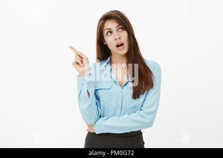 Dreamy empty-headed cute girl with brown hair, standing with opened mouth and lifted index finger while dreaming or spacing out, having no thoughts, trying to calculate something in mind - Stock Photo