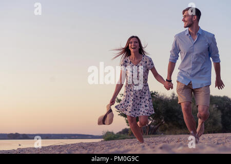 Couple walking on the beach at sunset - Stock Photo