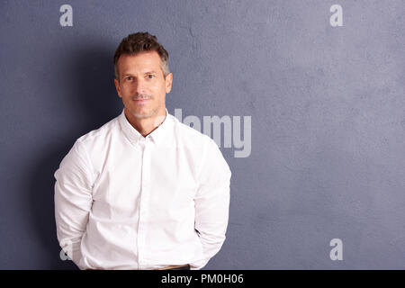 Portrait shot of a middle aged man wearing white shirt and looking at camera while standing at grey wall with copy space. - Stock Photo