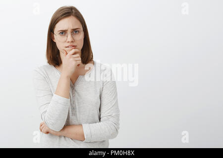 Cute female geek trying solve hard math riddle standing thoughtful over white wall rubbing chin during brainstorm looking at camera while making decision or thinking posing over gray background - Stock Photo