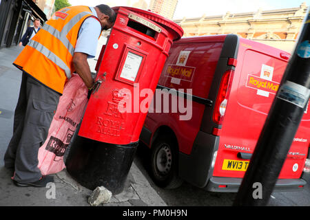 Royal Mail postal worker transferring mail into a sack bag from a red post box to his postal van in Charterhouse St Smithfield London UK  KATHY DEWITT - Stock Photo