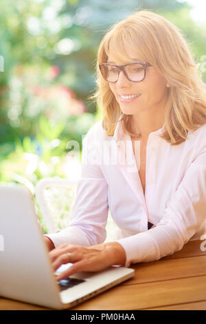 High angle portrait shot of attractive woman using laptop while working outside. Home office. - Stock Photo