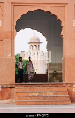 Lahore, Punjab, Pakistan, South Asia : Two chidren walk through an arch of the Badshahi Mosque, 1671-1673, the largest of the grand imperial mosques o - Stock Photo
