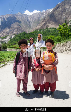 Karimabad, Hunza Valley, Gilgit-Baltistan, Pakistan : Two women and three school children on their way home pose for a portrait on the road from Altit - Stock Photo