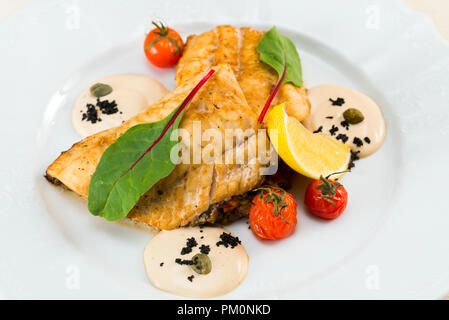fish fillet fried in sause with vegetables - Stock Photo