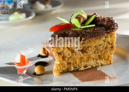cake with nuts and marmalade with chocolate cream on a plate - Stock Photo