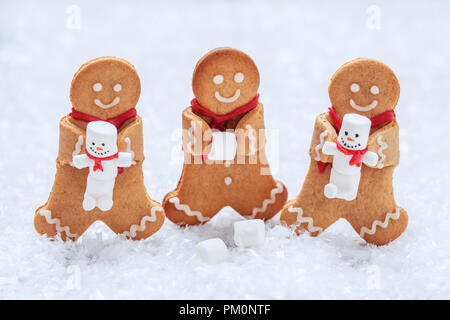 Funny Gingerbread cookie men with tiny marshmallow snowman - Stock Photo