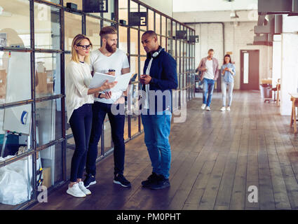 Sharing fresh ideas. Group of young business people in smart casual wear talking and smiling while standing in the office hallway. - Stock Photo
