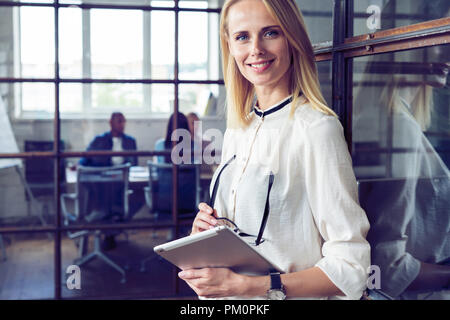 Leading her team to success. Confident young woman holding digital tablet and looking at camera with smile while her colleagues working in the background. - Stock Photo