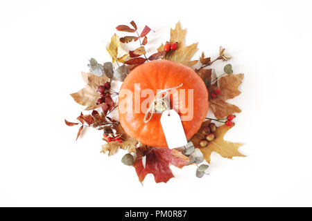 Autumn floral composition with orange pumpkin. Wreath made of dry maple, eucalyptus leaves and berries on white table background. Fall, Halloween and Thanksgiving design. Flat lay, top view. - Stock Photo