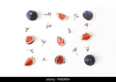 Fresh ripe purple figs. Food Photo. Creative composition of the whole and sliced exotic fruit and violet limonium flowers on a white table background. Floral pattern. Flat lay, view from above. - Stock Photo