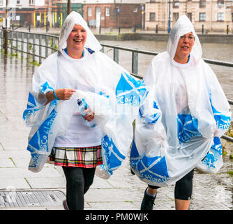 Leith, Edinburgh, Scotland, UK, 16th September 2018. Edinburgh Kilt Walk, the last of four kilt walks this year after those in Glasgow, Aberdeen and Dundee, sponsored by the Royal Bank of Scotland, takes place today. Walkers raise funds for a charity of their choice. There are three walk lengths: the full 24 miles from Holyrood Park to BT Murrayfield Stadium and two shorter walks of 15.5 and 5 miles. The kilt walkers reach The Shore at about Mile 14 in the rain. Two women wearing matching rain ponchos with saltires walk along the riverbank - Stock Photo