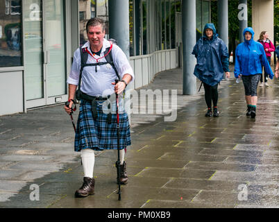 Leith, Edinburgh, Scotland, UK, 16th September 2018. Edinburgh Kilt Walk, the last of four kilt walks this year after those in Glasgow, Aberdeen and Dundee, sponsored by the Royal Bank of Scotland, takes place today. Walkers raise funds for a charity of their choice. The kilt walkers reach The Shore at about Mile 14 in the rain. An older man wearing a kilt and using walking poles walks along the riverbank - Stock Photo